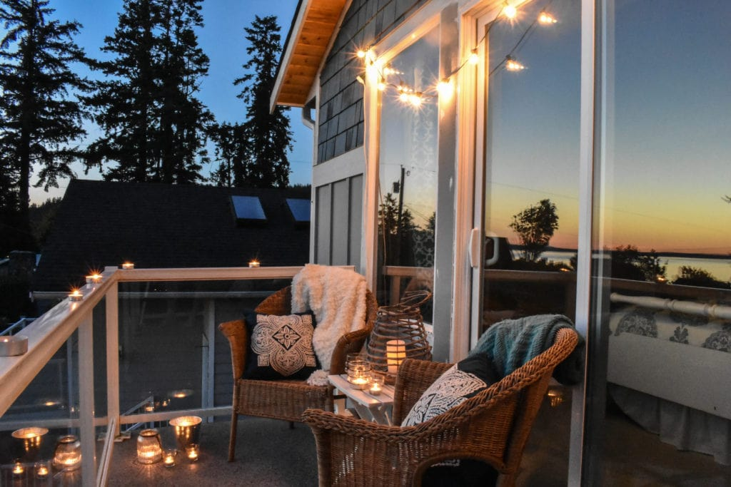 balcony with two chairs and a small table lit by string lights and candle lanterns