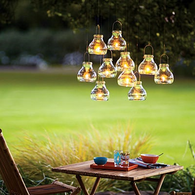 a group of mini candle lanterns suspended from a tree branch