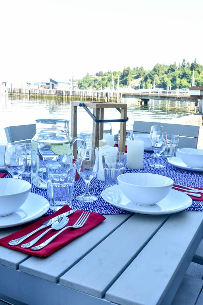 4th of July table set for a dinner party with red white and blue decorations on the waterfront