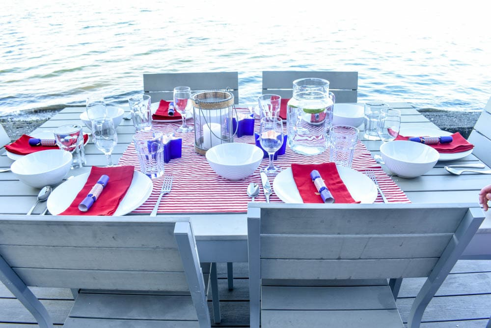 4th of July table set with red and white striped fabric and blue party poppers, with candle lanterns in front of Puget Sound