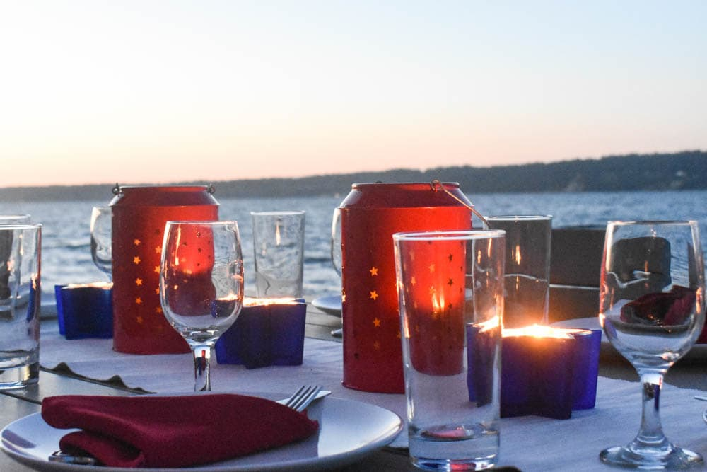 Independence Day table set with glowing red and white candle lanterns in front of Puget Sound