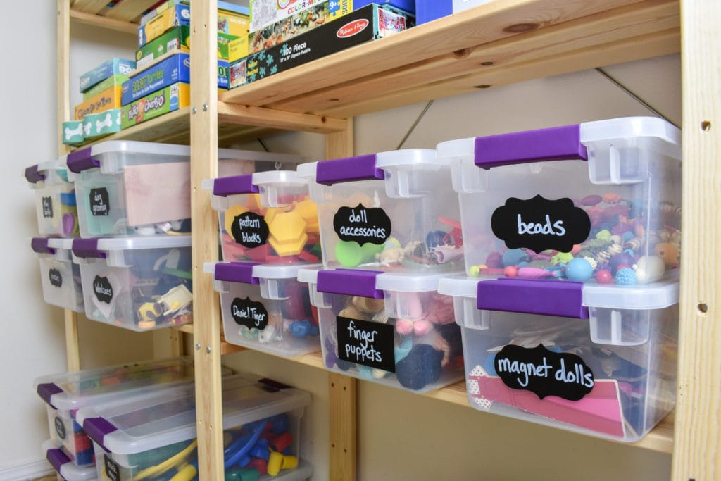 photo of organized toy closet with toy storage bins and wood Ikea shelving