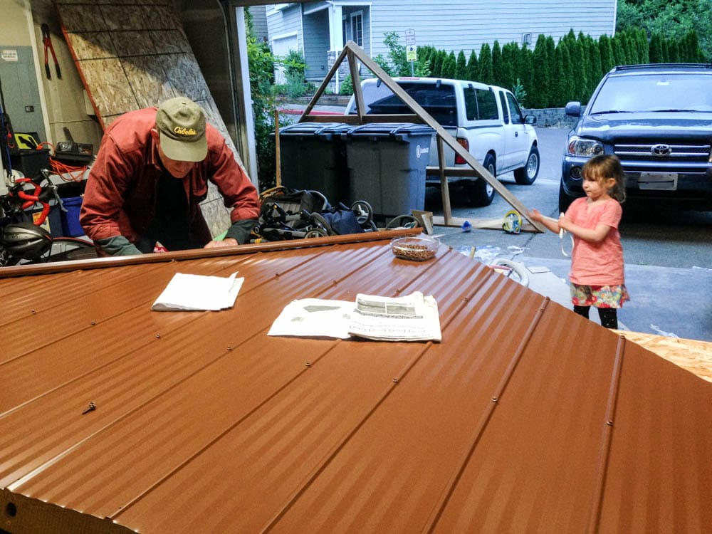 man and little girl assembling roof sections of Costco Gazebo by Yardistry Structures in a garage.