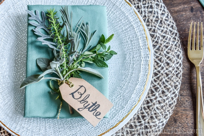 photo of holiday place setting with simple place card holder and fresh herbs