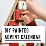 DIY Painted Advent Calendar: wood Christmas-tree-shaped advent calendar painted red and white with child's hands opening drawer