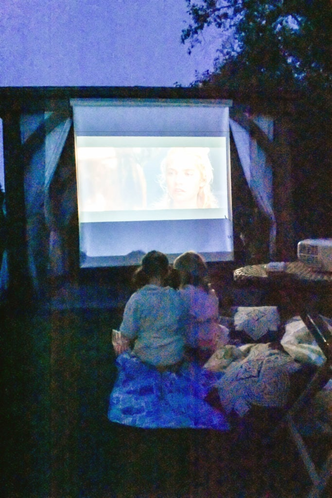 backyard movie theater set up using Costco Gazebo by Yardistry. Two little girls watching movie in foreground