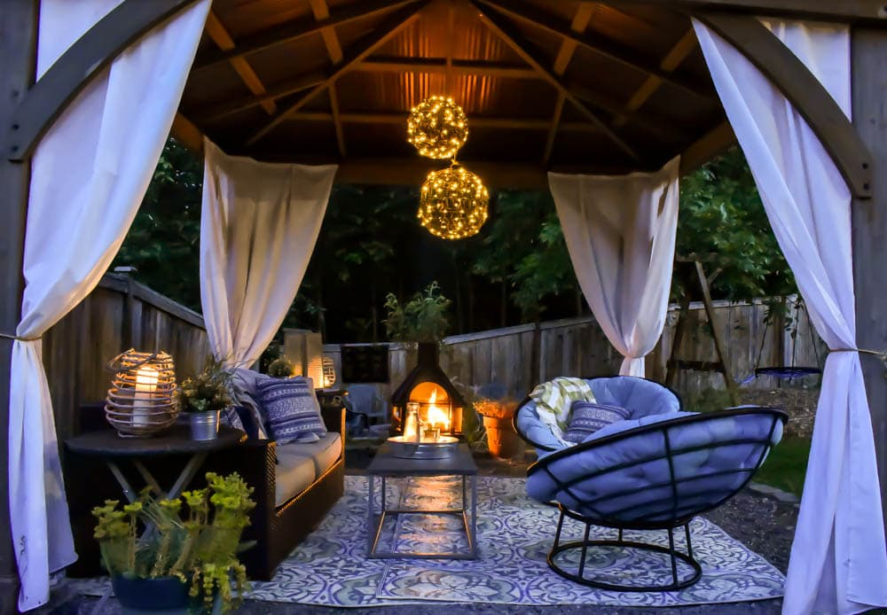gazebo outdoor living room patio shade idea in low light with outdoor curtains, chandelier, and outdoor fireplace