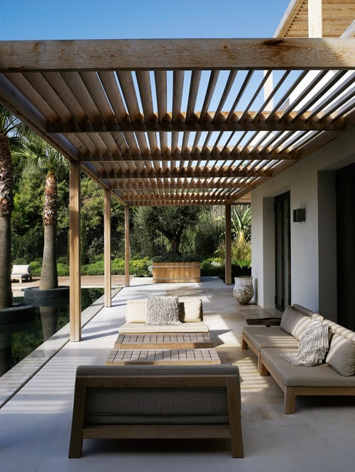 modern pergola structure patio shade idea with outdoor sofa and palm trees