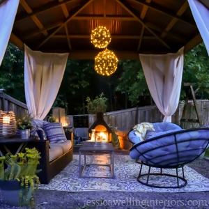 outdoor living room in gazebo with outdoor curtains, sofa, chandelier, and outdoor fireplace