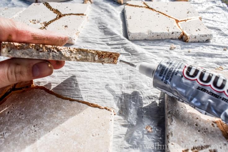 image of someone gluing broken tile together to make kintsugi coaster