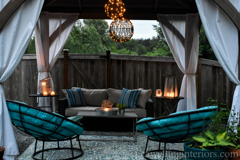 outdoor living space lit with an outdoor chandelier and glowing candle lanterns