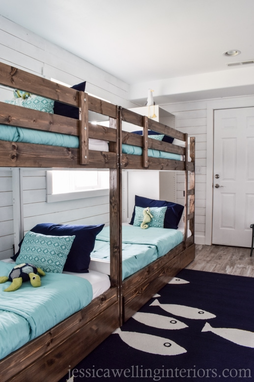 4 bunk beds in a beach themed bunk room with a navy fish rug and stuffed sea creatures on the beds