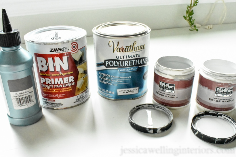 Five paint cans and samples lined up for DIY tile painting project- dark grey grout refresh, BIN primer, polyurethane clear coat, and two Behr paint samples in white and grey
