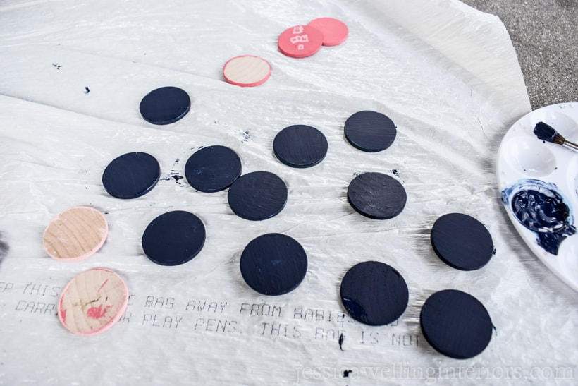 wood coins being painted with acrylic paint and laid out to dry