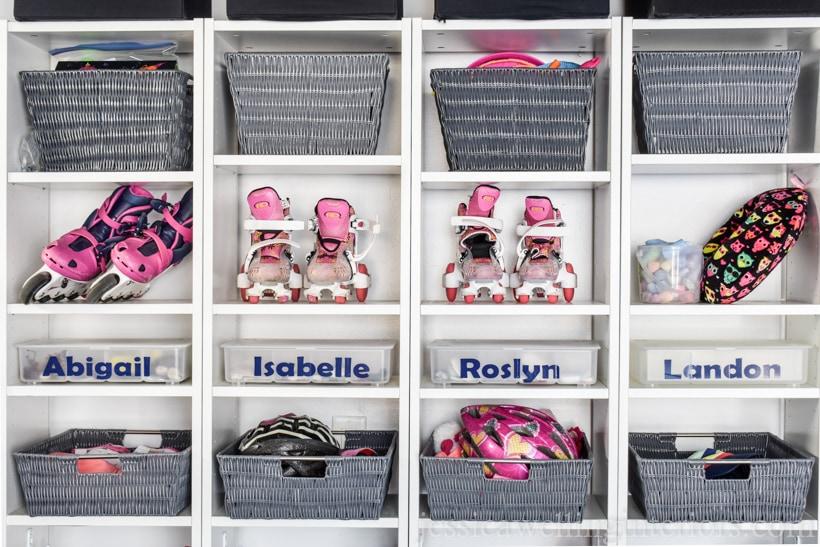 close-up of 4 Billy bookcases from Ikea lined up to make a backpack organizer. Top shelves hold rollerskates, bike helmets, and storage baskets