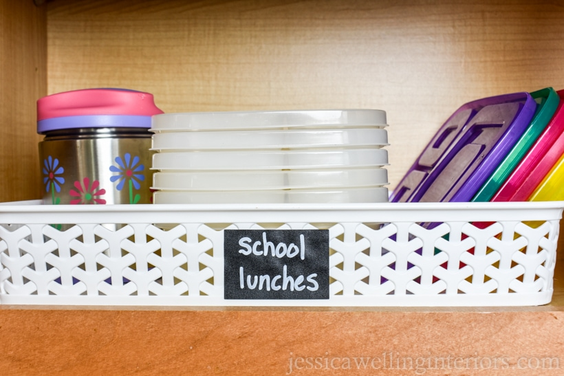 "kitchen cupboard with basket labeled ""school lunches"" and thermos and stack of bento containers with lids"
