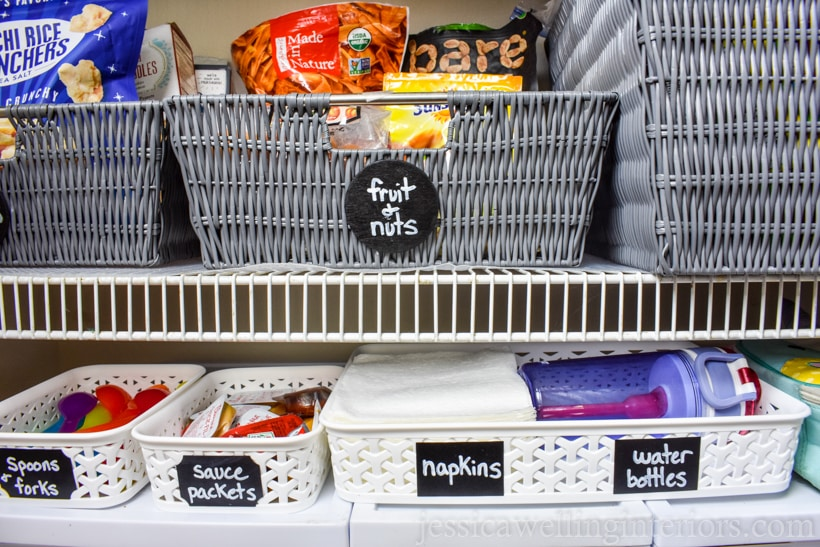 school lunch-packing station inside bottom of pantry closet with baskets for spoons & forks, sauce packets, napkins, and water bottles