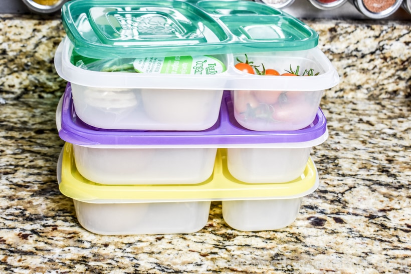 stack of three bento lunch containers packed on kitchen countertop