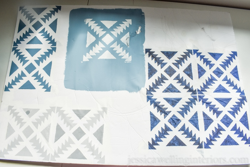 white cardboard test piece with painted Aztec stencil in differing shades of blues and grey