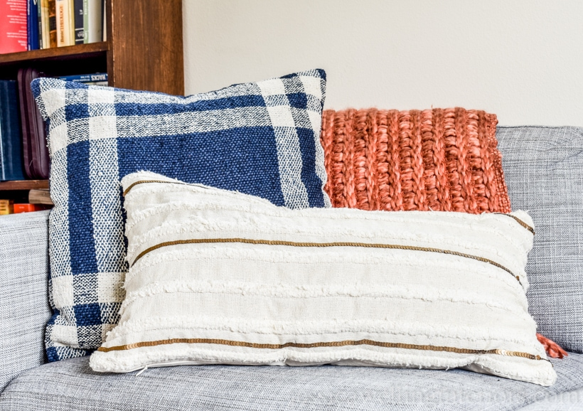 Fall living room decor with navy and white plaid throw pillow, burnt orange chunky throw blanket, and white boho lumbar pillow