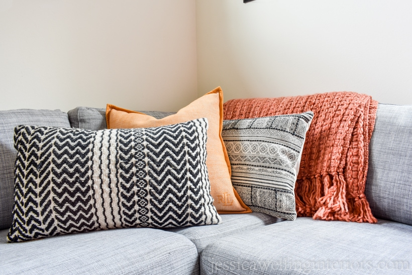 living room sofa decorated for Fall with burnt orange chunky throw blankets, tribal black and white patterned throw pillows, and a yellow pillow