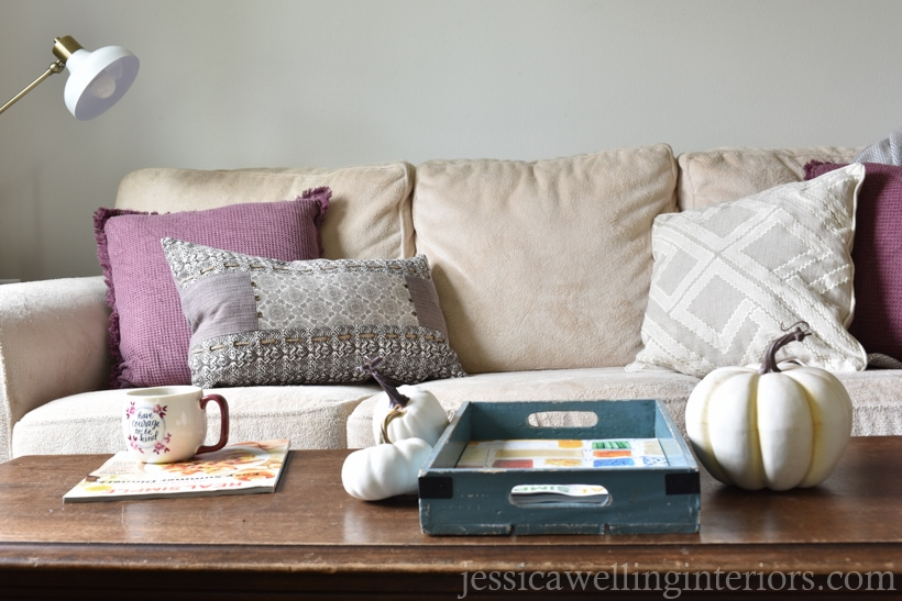 neutral and plum purple Fall living room decor with cream colored sofa, plum and white pillows, and white pumpkins on wood coffee table in foreground