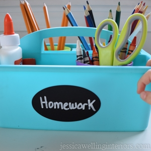 "aqua blue plastic caddy labeled ""homework"" and filled with crayons, glue, scissors, pencils, etc."