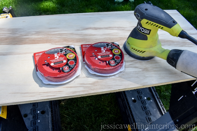 cut plywood piece sitting on two sawhorses, with orbital sander and sandpaper discs sitting on top of it