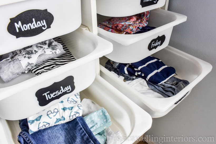 IKEA TROFAST unit with each drawer bin labeled with a chalkboard sticker label and filled with a single outfit