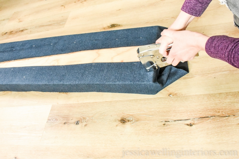 hand using staple gun to wrap and staple the fabric on the end of upholstered bench seat cushion for window seat