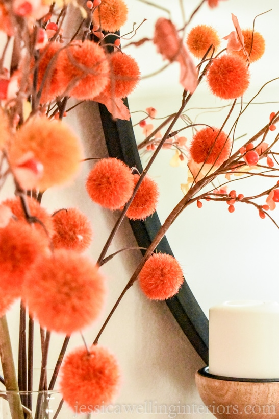 Fall mantel decor close-up of pom-pom stems in front of a round mirror