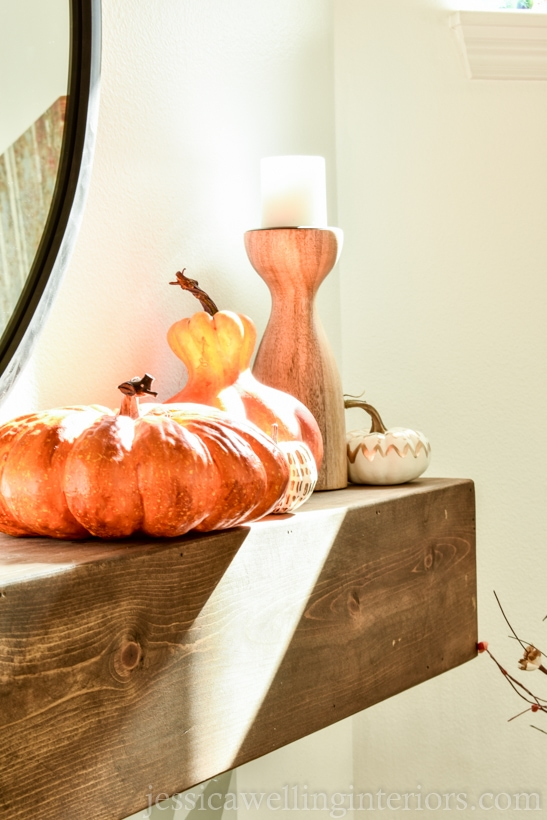 close-up of orange and yellow pumpkins sitting on a wood mantle decorated for Fall