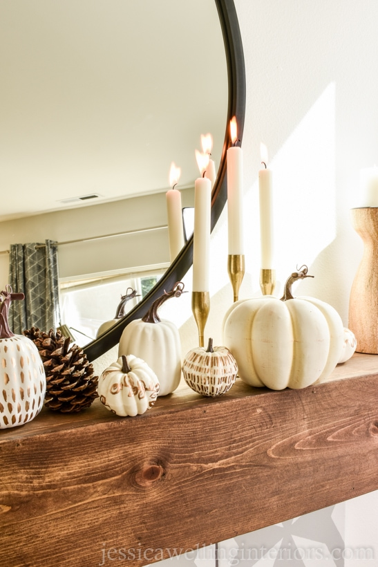 wood mantel with white painted pumpkins, gold candlesticks, and a pinecone