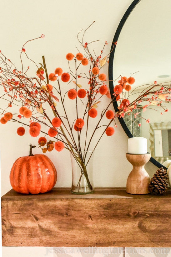 orange and red pom-pom stems in a glass vase sitting on a wood mantle decorated for Fall with a round mirror, candle holder, and orange pumpkins