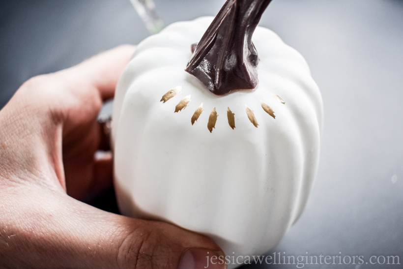 white pumpkin being painted with gold leaf paint for Fall decor ideas