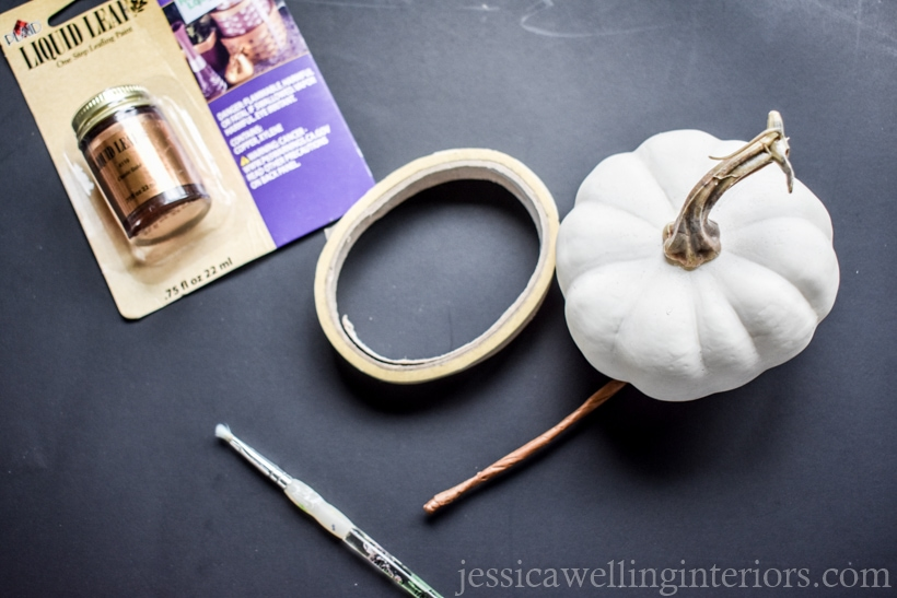 supplies to paint pumpkins for Fall decor- white faux pumpkin, gold leaf paint, small paintbrush, and masking tape against a black background