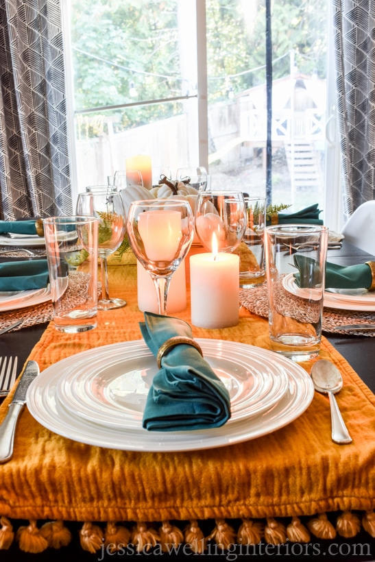 thanksgiving table setting with mustard colored table runner, candles and glasses
