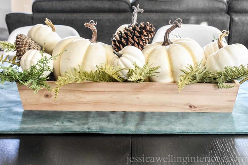 simple white pumpkin centerpiece with pumpkins in a wood tray with foliage and pinecones