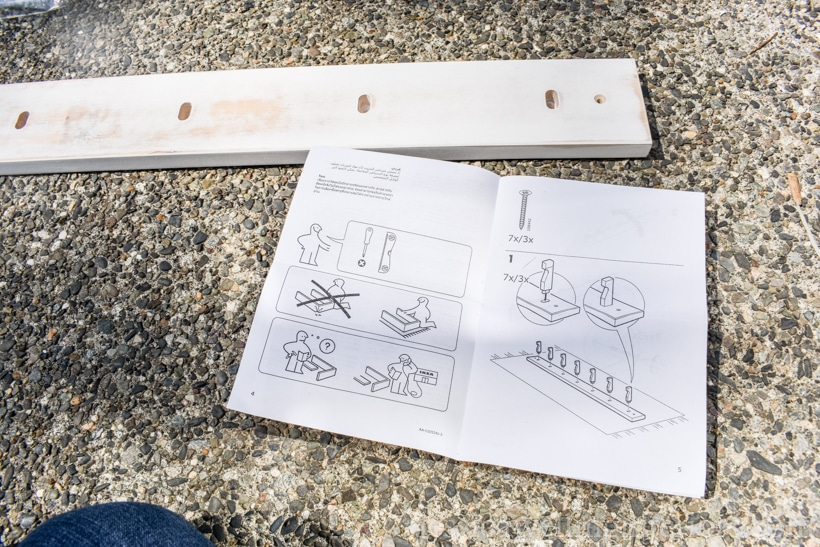 IKEA KUBBIS coat hooks rack laying on cement patio, with assembly instructions out