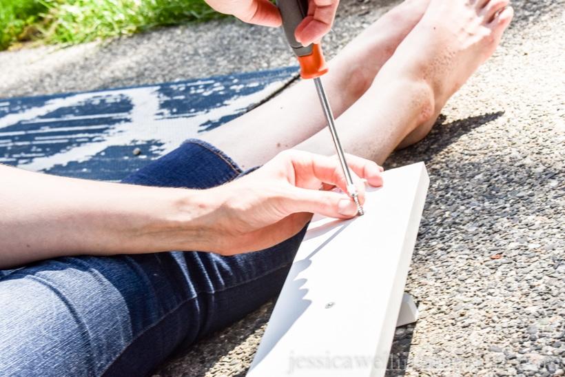 woman using screwdriver to assemble IKEA KUBBIS coat hooks rack on patio