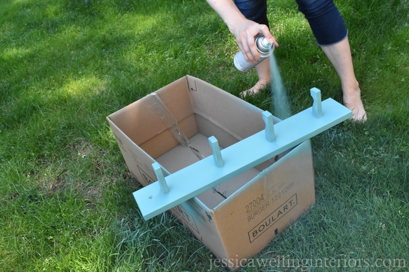 woman applying second coat of aqua-colored spray paint to modern coat hooks rack outdoors in grass