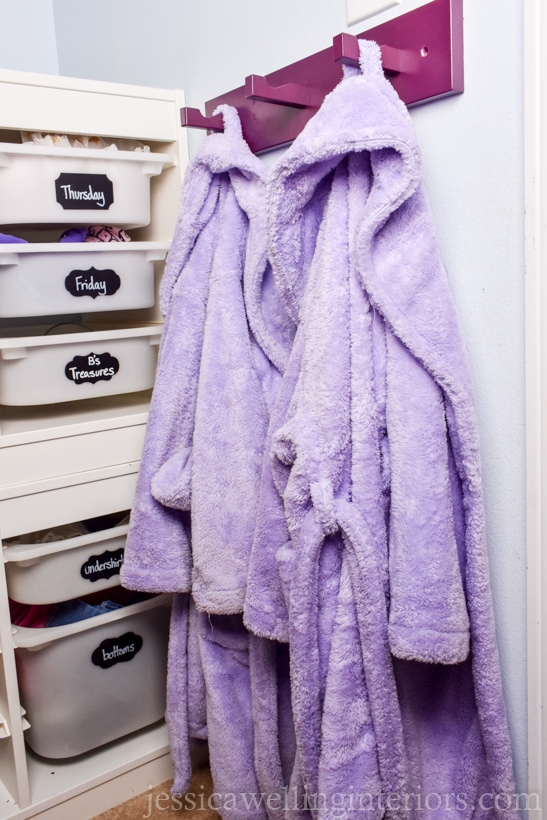 purple-painted modern coat hooks rack for kids room organization with lavender-colored bathrobes hanging from it