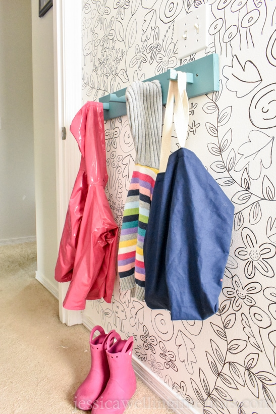 finished modern coat hooks rack with children's coats and bag hanging from it