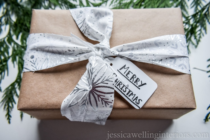 Christmas gift wrapped in brown paper and tied with white and silver fabric ribbon with snowflake pattern