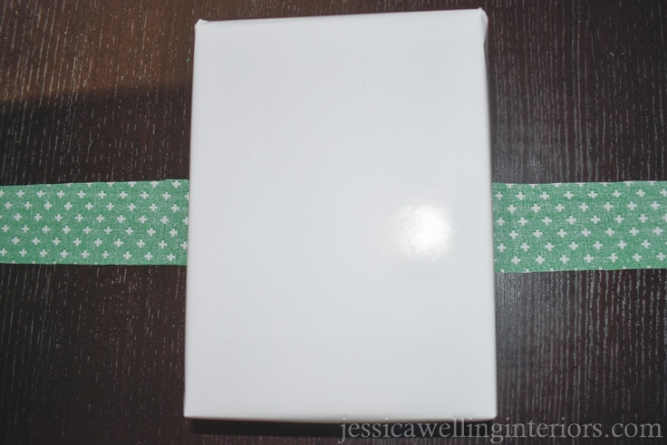 Christmas gift wrapped in solid white wrapping paper, laying on top of strip of green fabric