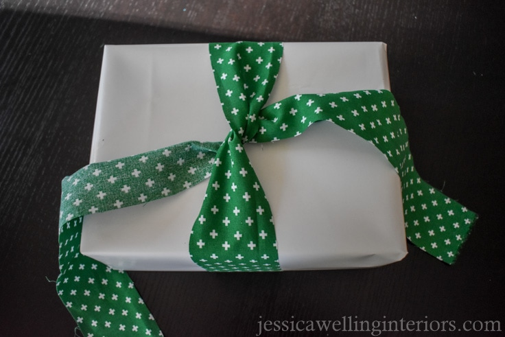 "green fabric ""ribbon"" being tied in a knot on top of white-paper wrapped Christmas gift"