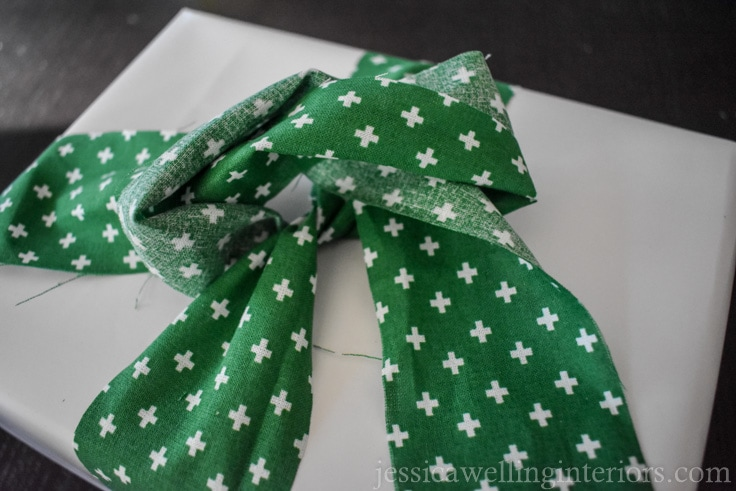 "green fabric ""ribbon"" being tied around white wrapped holiday gift"