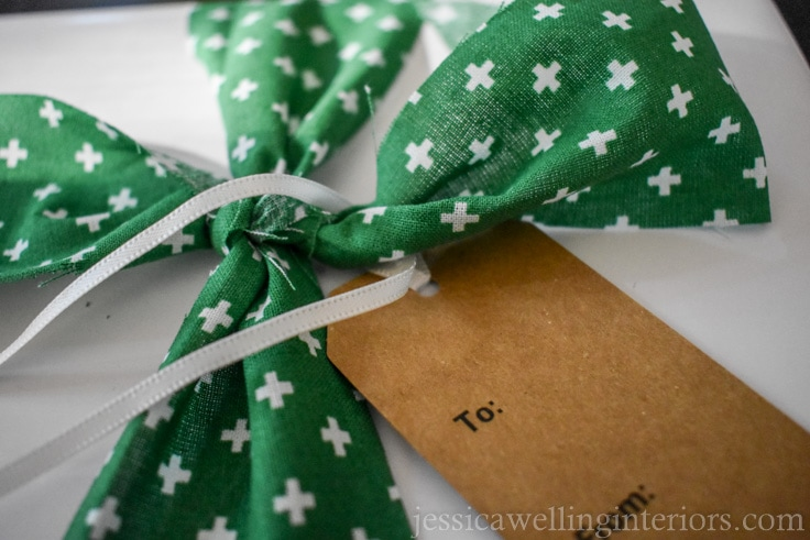 brown paper gift tag being tied onto wrapped gift