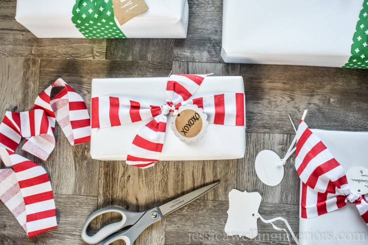 Christmas gift wrapping with white paper and candy cane striped fabric bows.