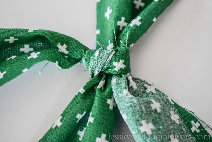 "green fabric ""ribbon"" being tied in a double knot around white paper wrapped Christmas gift"